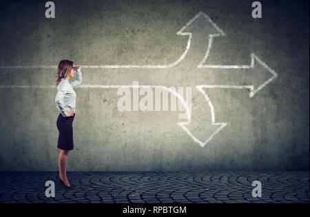 Confident businesswoman looking into the future as a crossroad arrows split in three different ways. Choosing the right way making difficult decision  - Stock Photo