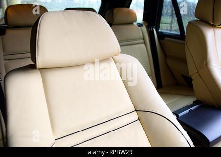 Luxury car inside. Interior of prestige modern car. Comfortable leather seats. Beige stitched leather cockpit.
