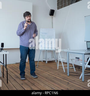Male warning. Teacher warning students from mistakes. Man in casual clothing. Professor lecturing at classroom with wooden floor. Caucasian teacher - Stock Photo