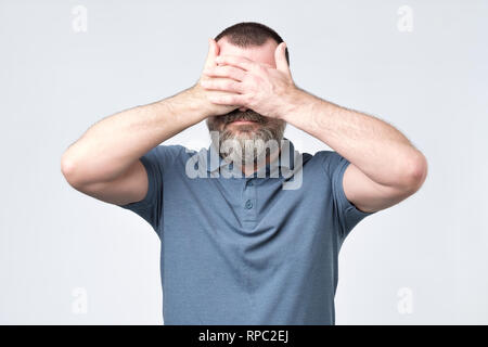 Man in blue t-shirt covering his face with hands - Stock Photo