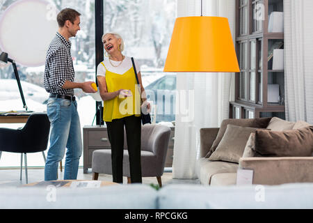 Elegant fancy elderly woman selecting new couch with good-appealing son - Stock Photo