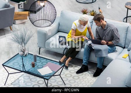 Senior stylish lady advising nice-looking son with selecting furniture - Stock Photo