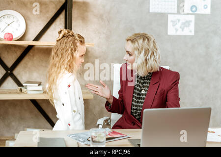 Resolute mother in red jacket having serious conversation - Stock Photo