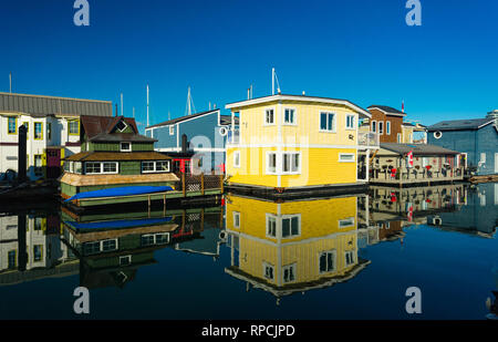 The colorful village of float homes on a bright sunny day, blue sky. - Stock Photo