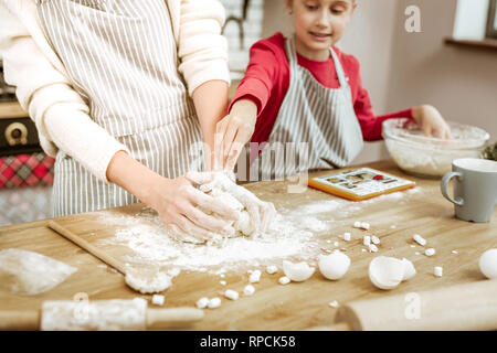 Mother having dirty hands because of working with dough - Stock Photo