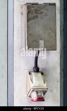 Main electrical outlet with the metal box on the cement wall for use in the old factory. - Stock Photo