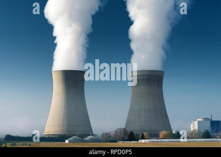 two power plant cooling towers steaming on dark blue sky background - Stock Photo