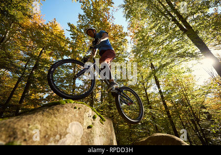 Professional cyclist jumping on trial bicycle on big boulder. Low angle view of male rider making acrobatic trick in the forest on summer sunny day. Concept of extreme sport active lifestyle - Stock Photo
