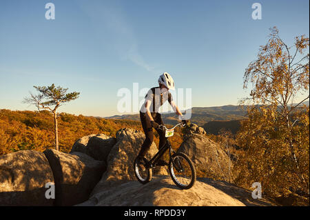 Young male cyclist balancing on trial bicycle on top of big boulder, rider making acrobatic stunt on summer evening, blue sky and forest on background. Concept of extreme sport active lifestyle - Stock Photo
