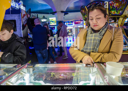 A mother and son play two penny falls in an amusement arcade in Bournemouth, Dorset, UK - Stock Photo