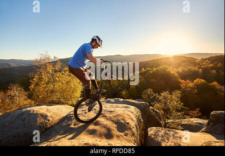 Professional cyclist riding on back wheel on trial bicycle. Sportsman rider balancing on the edge of big boulder on the top of mountain at sunset. Concept of extreme sport active lifestyle - Stock Photo