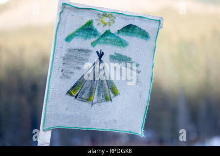 Camping flag showing a simple indian tent with mountains and sun in the back, hand drawn on a white hemp cloth. Blurry background with grass, during S - Stock Photo