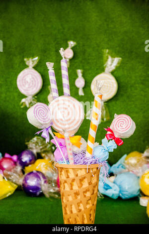 Decorations for the party. Huge colored pink lolly-pops from paper and fabric in the big basket. Green background - Stock Photo
