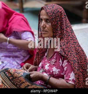 Native woman doing embroidery work, Jaisalmer Fort, Jaisalmer, Rajasthan, India - Stock Photo