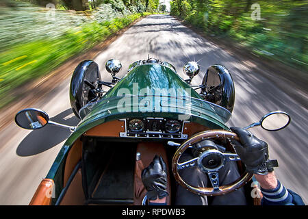 Morgan 3-Wheel car being driven fast through an English country lane with blurred scenery and an impresion of speed. Release signed. - Stock Photo