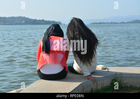 Muslim girls by the sea - back view - Stock Photo