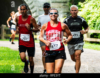 Babylon, New York, USA - 12 August 2018: Runners on a dirt path in the woods racing a 10K for charity in the summer enjoying their day. - Stock Photo