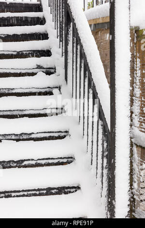 Exterior wooden stairway exposed to winter snow fall rendering access unsafe until cleared - Stock Photo