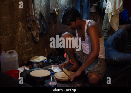 Traditional making of the staple food chapati is a timeless art. Here seen cooked for fellow workers in Dhobi Ghat, Mumbai - Stock Photo