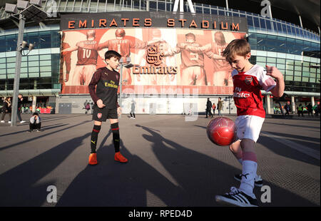 Young Arsenal fans playing football outside the ground before the game during the UEFA Europa League round of 32 second leg match at the Emirates Stadium, London. - Stock Photo
