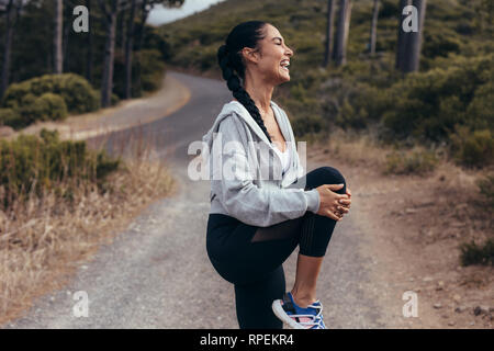Fitness woman stretching her leg before a run. Female runner doing stretching workout outdoors and smiling. - Stock Photo