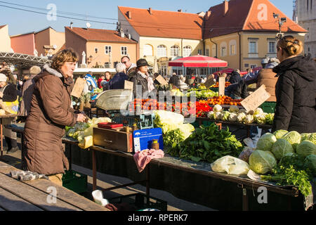Zagreb, Croatia - December 29th 2018. A stall holder waits for customers at the Dolac fresh fruit and vegetable market in Central Zagreb - Stock Photo