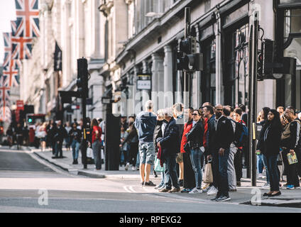 LONDON, UNITED KINGDOM - MAY 18, 2018: Pedestrians waiting to cross the Regent Street in London on a warm spring day  - Stock Photo