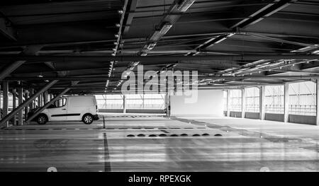 White van parked in modern airport parking - black and white wide image - Stock Photo