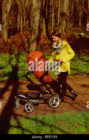 Mother push baby stroller in spring park. Young mother with pram on walk. Nothing feels as good as being a mom - Stock Photo