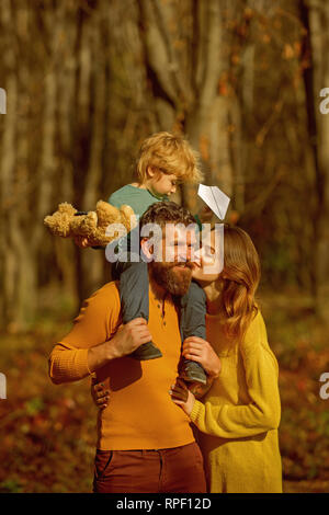 Young family of mother and father piggybacking little son in park on vacation. Small child and parents on vacation. Creative holidays - Stock Photo