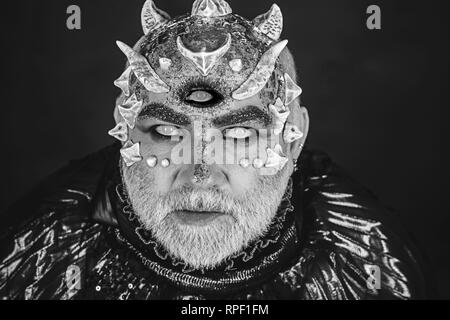 Alien, demon, sorcerer makeup. Horror and fantasy concept. Head with third eye, thorns or warts. Demon on black background, close up. Senior man with - Stock Photo