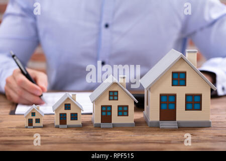 Close-up Of Businessman Calculating Invoice Using Calculator With House Model On Office Desk - Stock Photo
