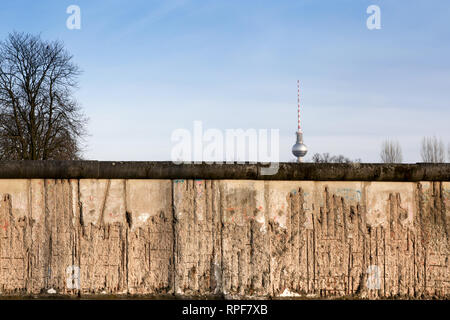 Berlin Wall original weathered section damaged with exposed iron bars partly covering the TV tower (Berliner Fernsehturm) far in the horizon. - Stock Photo