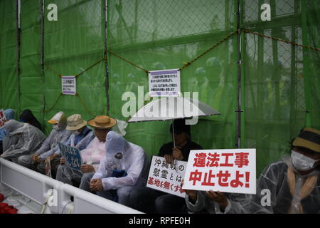 Nago, Japan. 22nd Feb, 2019. Protesters with placards block construction vehicles from entering the construction site during anti U.S. base protest outside of the U.S Base Camp Schwab gate on February 22, 2019 in Nago, Okinawa prefecture, Japan. Anti-U.S base protesters stage a sit-in protest at the gate of the U.S. Marine Corps' Camp Schwab blocking the passage of construction vehicles mobilized by the Japanese government to slow down the on-going relocation of the new U.S Airbase Station in Henoko. A prefectural referendum is scheduled for Feb. 24 on the planned relocation of the U.S base. C - Stock Photo