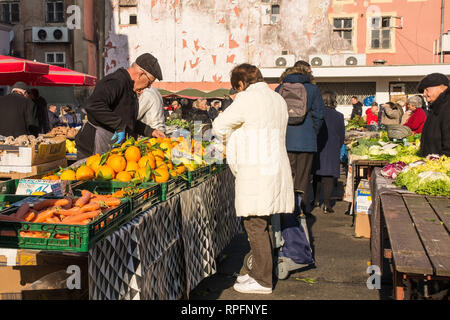 Zagreb, Croatia - December 29th 2018. A stall holder serves a customer at the Dolac fresh fruit and vegetable market in Central Zagreb - Stock Photo