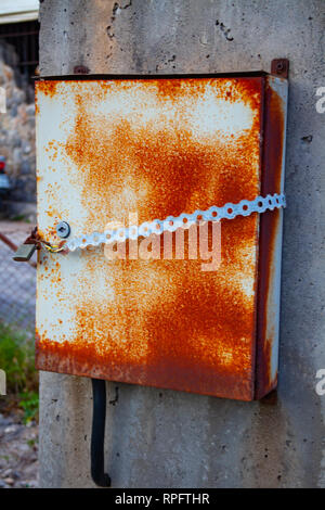 Old rusty electricity installation box on the wall. Brown rust on the metal - Stock Photo