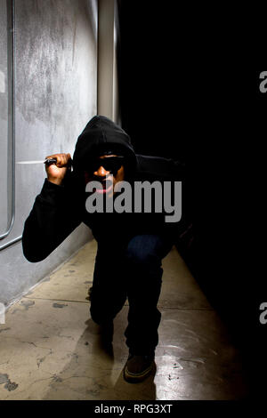 hooded criminal with a knife hiding in the shadows of a street alley - Stock Photo
