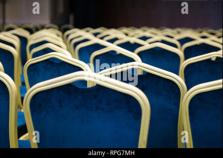 Empty cinema auditorium. a large number of blue velvet chairs in a row. - Stock Photo
