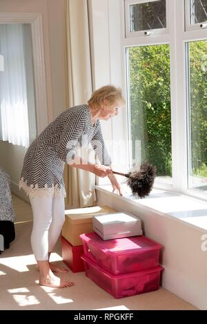 House Move; Woman using an Ostrich feather duster to dust her home - Stock Photo