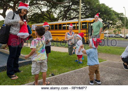 Group of young children wearing a Santa hat stocking caps before excursion, Kahala, Honolulu, Oahu, Hawaii, USA - Stock Photo