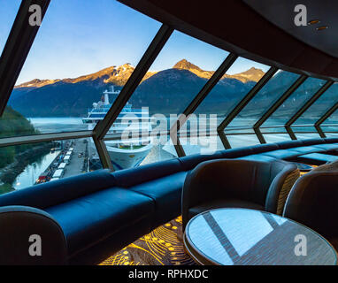 September 15, 2018 - Skagway, AK:  Sunrise on mountains and Princess Cruises ship berthed in port, early morning  from inside a quiet Crow's Nest Loun - Stock Photo