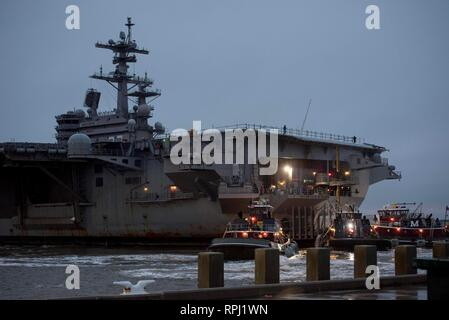 190221-N-KO018-0071 NORFOLK, Va. (Feb. 21, 2019) Tugboats attach lines to the fantail of the aircraft carrier USS George H.W. Bush (CVN 77) at Pier 12 onboard Naval Station Norfolk. GHWB is at Norfolk Naval Shipyard undergoing a Docking Planned Incremental Availability (DPIA). (U.S. Navy photo by Mass Communication Specialist Seaman Carson J. Davis) - Stock Photo