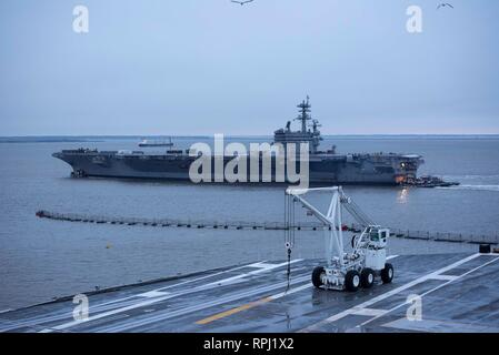 190221-N-KO018-0113 NORFOLK, Va. (Feb. 21, 2019) Tugboats assist as the aircraft carrier USS George H.W. Bush transits the Elizabeth River. GHWB is at Norfolk Naval Shipyard undergoing a Docking Planned Incremental Availability (DPIA). (U.S. Navy photo by Mass Communication Specialist Seaman Carson J. Davis) - Stock Photo
