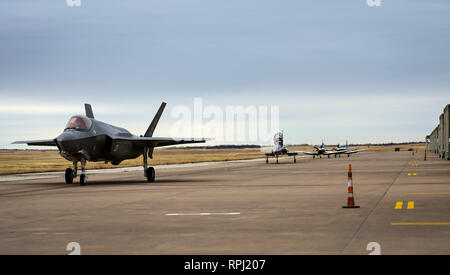 An F-35A Lightning II taxis to a parking spot as aircraft from the 80th Flying Training Wing's Euro-NATO Joint Jet Pilot Training program taxi out for a training mission at Sheppard Air Force Base, Texas, Jan. 10, 2019. Four F-35s from Eglin AFB, Fla., stopped at Sheppard as part of an undergraduate pilot training base road tour to show the aircraft to ENJJPT student pilots as well as provide capability briefings. Some F-35 aircraft maintenance Airmen in training from the 82nd Training Wing were also able to get an up close look at the fifth-generation fighter and talk with active duty mainten - Stock Photo