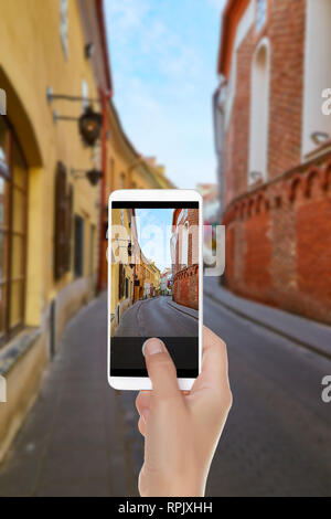 A man is making a photo of empty street in old town of capital of Lithuania - Vilnius on a mobile phone - Stock Photo