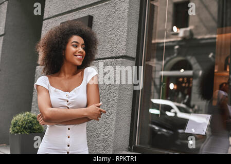 Young and full of energy. Portrait of gorgeous Afro American woman standing outdoors with crossed arms and smiling. Fashion look - Stock Photo