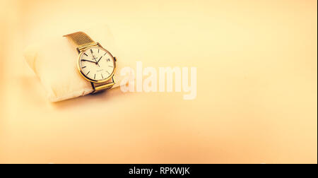 Seville, Spain - February 9 2019: Gold  Omega Geneve Automatic vintage wristwatch on colored background,  showing 13:50:59 on the 27st - Stock Photo