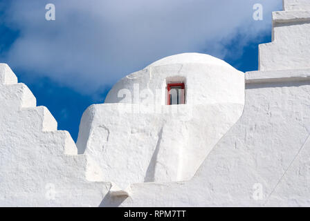 Church dome with small window in Mykonos, Greece. Chapel building architecture detail. White church on cloudy blue sky. Religion and cult concept. Summer vacation on mediterranean island. - Stock Photo