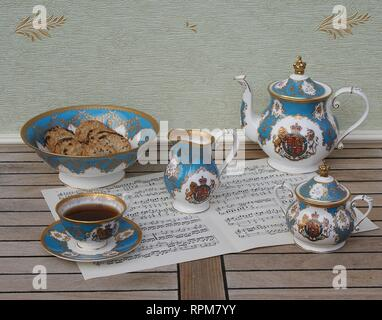 English teacup with saucer, teapot, sugar bowl, cream jug and a cake bowl with cookies, fine bone china porcelain, on a sheet of music - Stock Photo