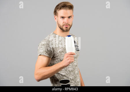 Man strict face holds shampoo bottle, grey background. Man enjoy freshness after washing hair with shampoo. Guy with hairstyle holds bottle shampoo, copy space. Hair care and beauty supplies concept. - Stock Photo